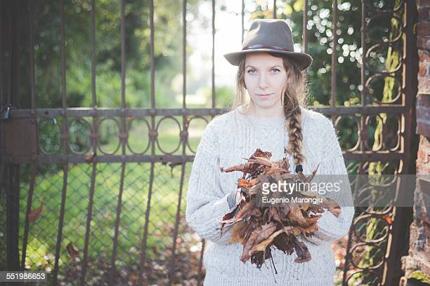 Young woman collecting autumn leaves