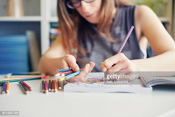 Young woman colouring in an adult colouring book