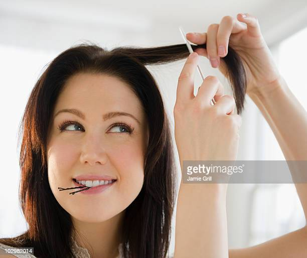 Young woman combing and styling her hair