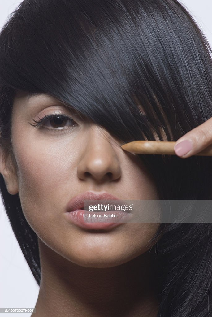 Young woman combing hair, close-up, portrait : Stock Photo