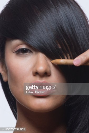 Young woman combing hair, close-up, portrait : Photo