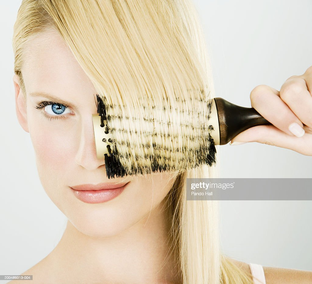 Young woman combing hair, portrait, close-up : Stock Photo