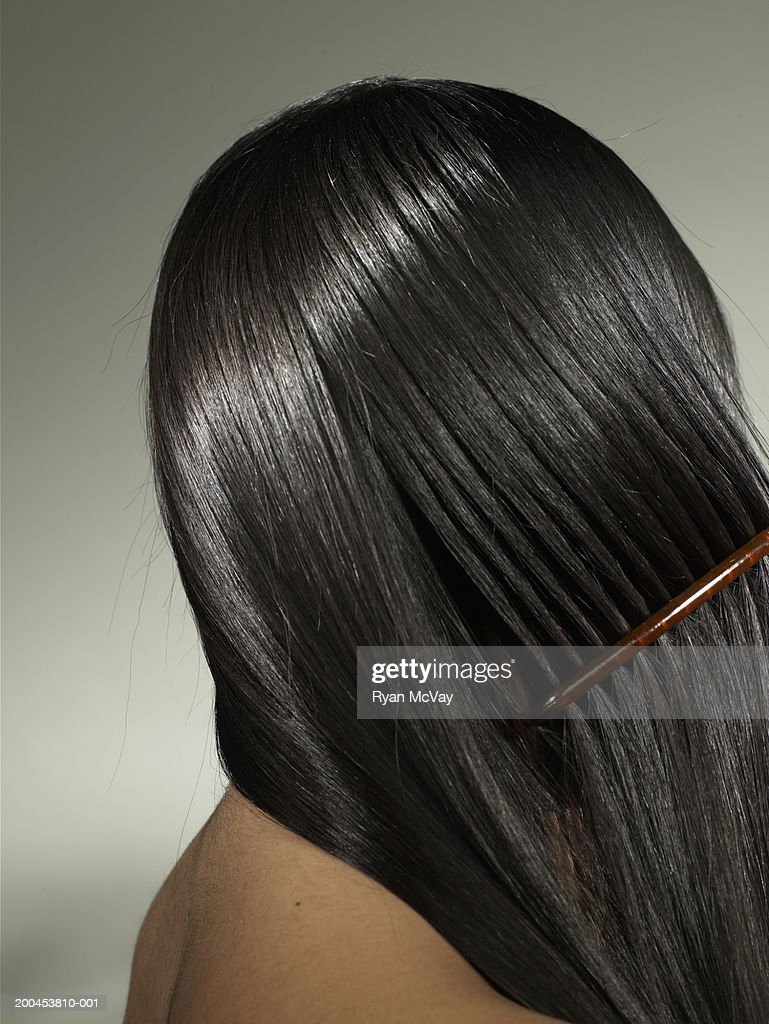 Young woman combing hair, side view : Stock Photo
