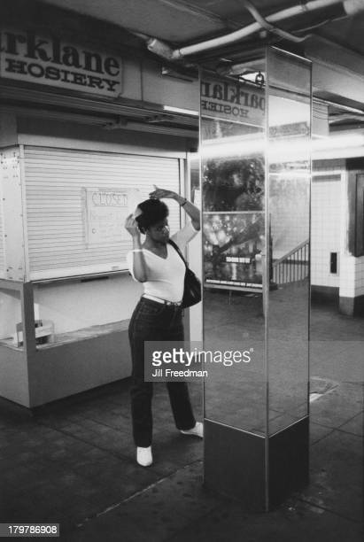 A young woman combs her hair using a pillar as a mirror Midtown Manhattan New York City 1983