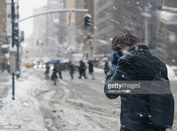 Young woman communicating on cell phone in snow