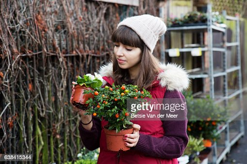 Young woman compares winter plants in urban garden center.