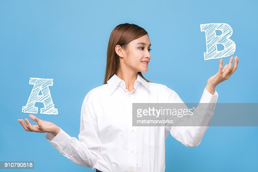 Young woman comparing A with B. : Stock Photo