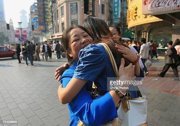 A young woman conducting the 'freehugs' campaign embraces a stranger at the Nanjing Road Shanghai's main shopping street on November 4 2006 in...