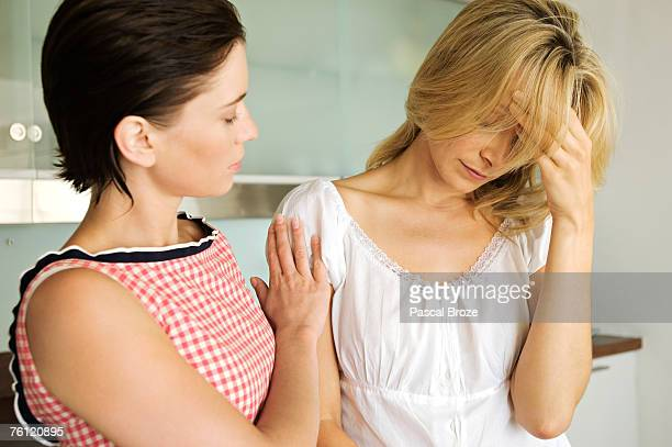 Young woman consoling another