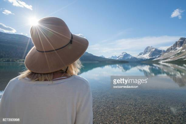 Young woman contemplating nature at mountain lake