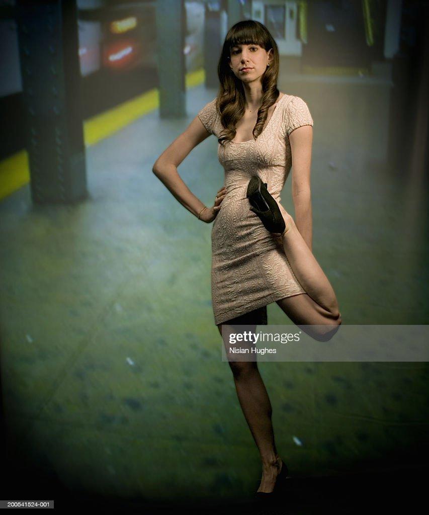 Young woman, contorting leg on subway platform