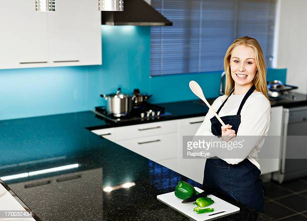 Young woman cook looks proud and pleased with modern kitchen