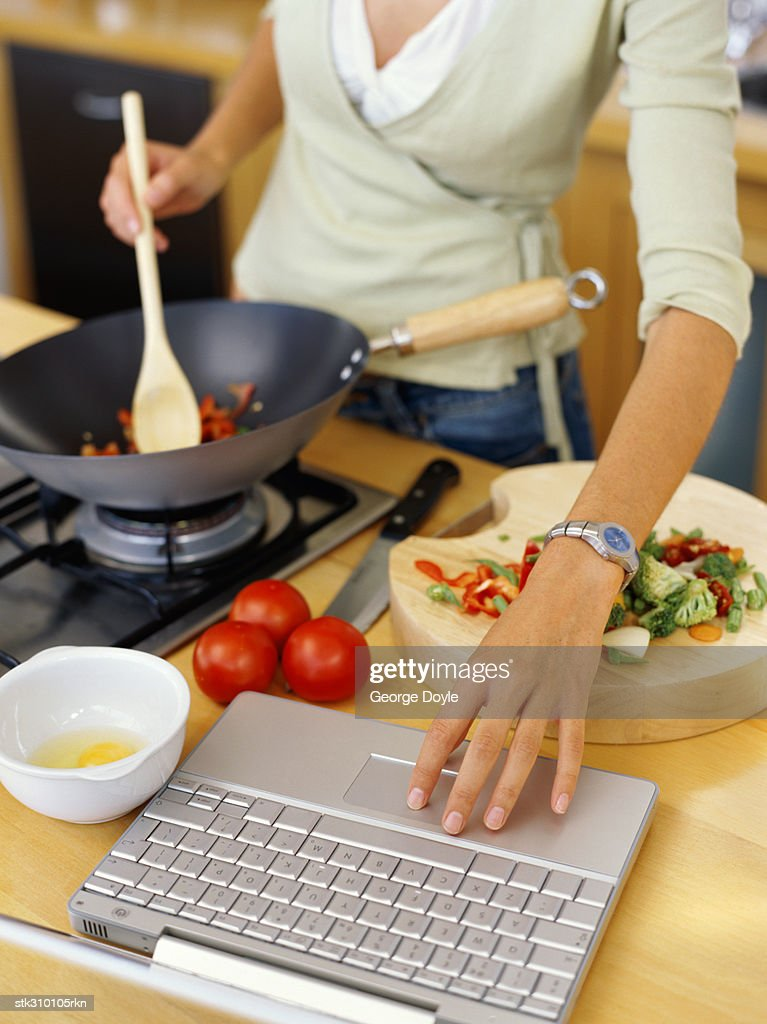 young woman cooking food and using a laptop in the kitchen : Stock Photo