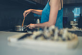 A young woman is cooking and stirring a pot