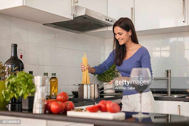 Young woman cooking spaghetti in kitchen