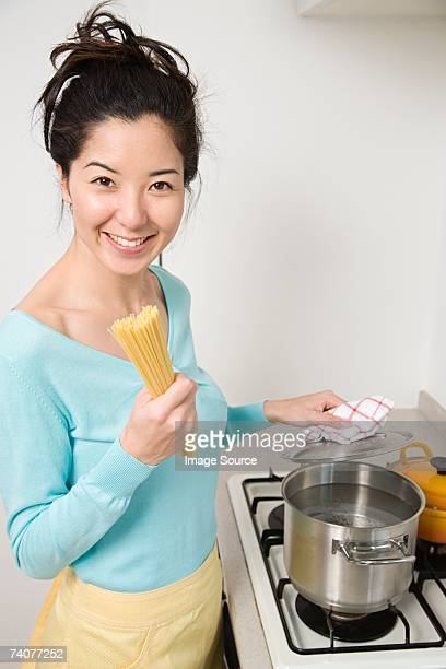 Young woman cooking spaghetti