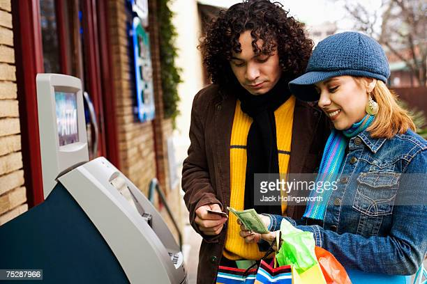 Young woman counting money in front of ATM machine