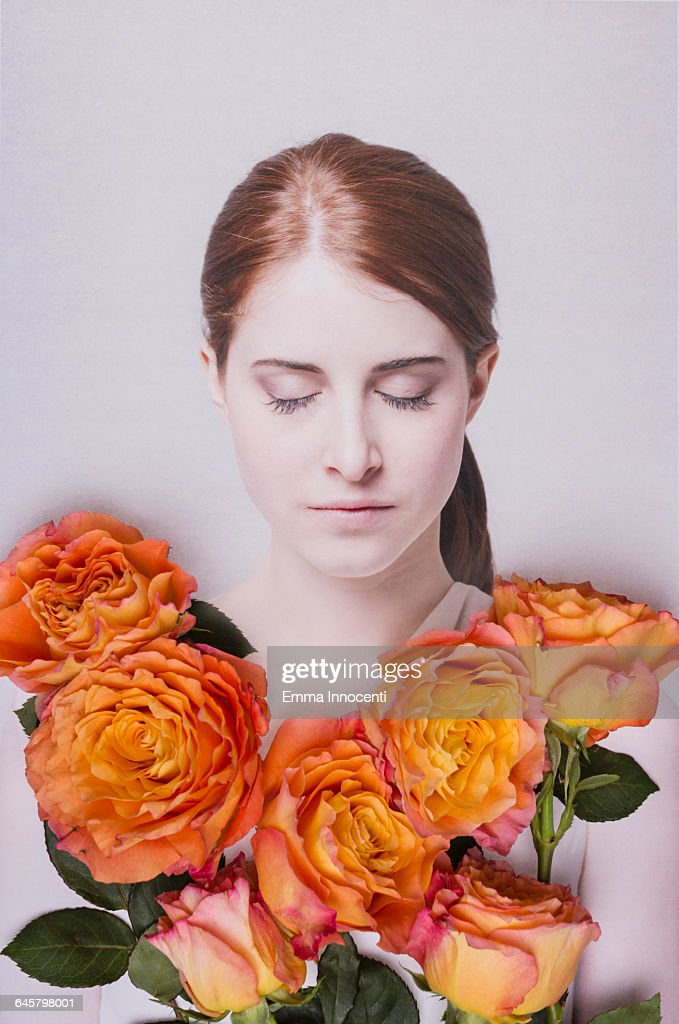 Young woman covered by flowers