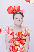 Young woman covered by rose petals