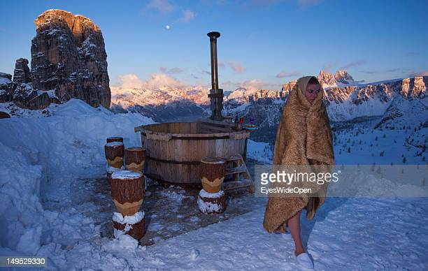A young woman covered in a blanket is getting out of the hot bath tub of the alpine mountain hut Rifugio Scoiattoli that faces the famous rocks...