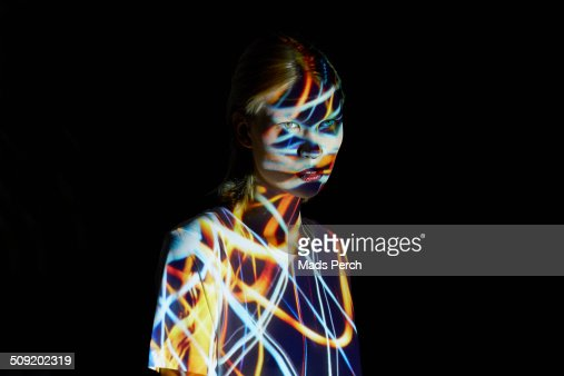 Young Woman covered in colorful lights