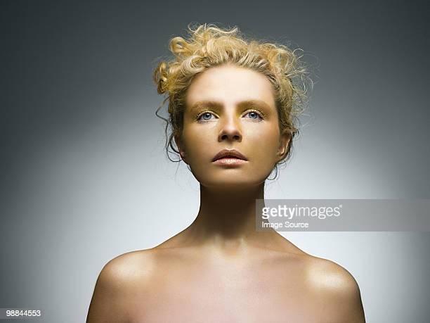 Giovane donna coperta in oro make-up