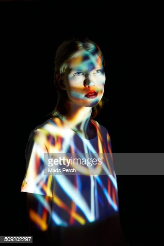 Young Woman covered in multicolored lights
