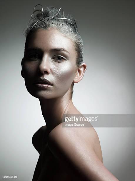 Junge Frau, die mit Silber-make-up