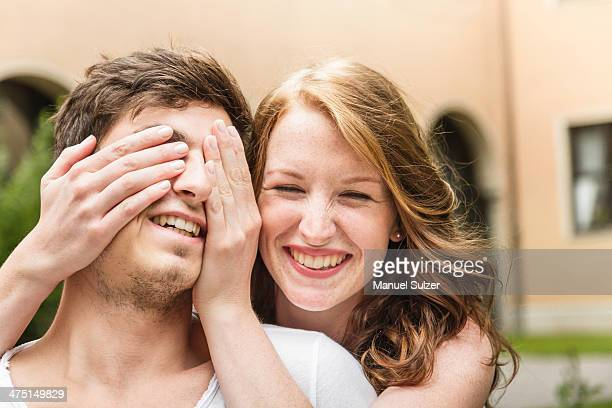 Young woman covering boyfriend's eyes