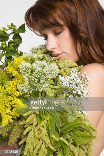 Young woman covering breast with flowers : Stock Photo