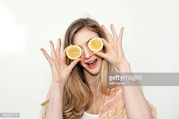 Young woman covering her eyes with lemons