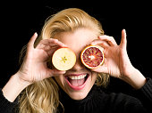 Young Woman Covering Her Face With Fruit Laughing