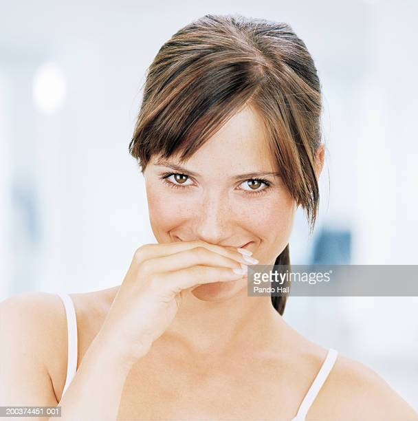 Young woman covering mouth with hand, smiling, portrait, close-up