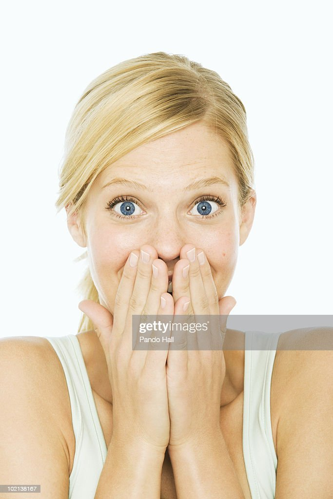 Young woman covering mouth with hands, laughing : Stock Photo