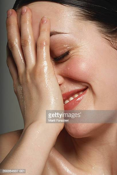 Young woman covering wet face with hand, smiling, close-up