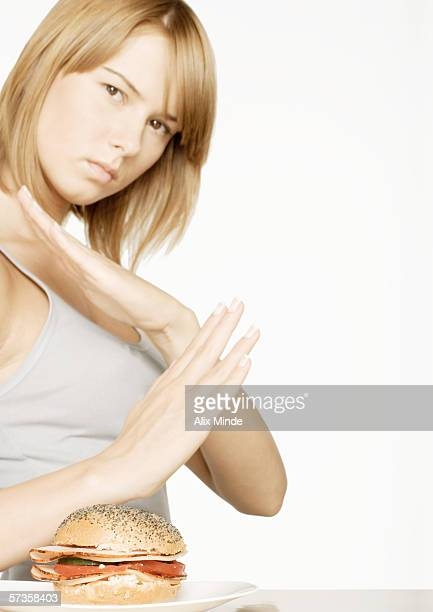 Young woman crossing arms, looking at sandwich