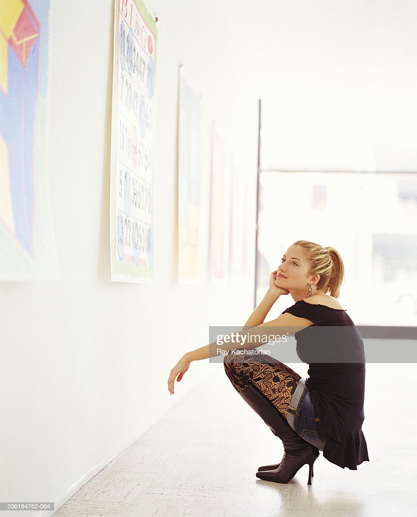 Young woman crouching in front of painting in gallery