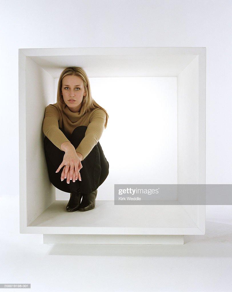 Young woman crouching inside white box