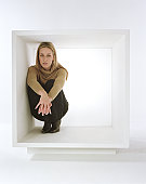 Young woman crouching inside white box