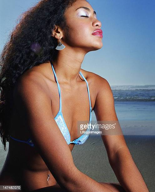 Young woman crouching on beach, eyes closed