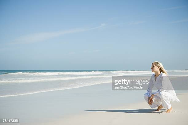 Young woman crouching on beach