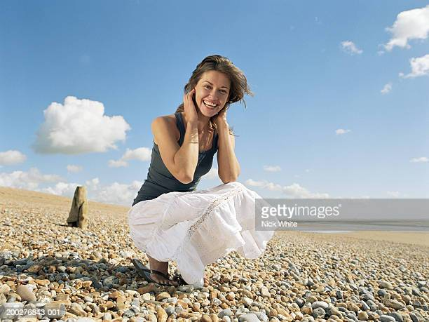 Young woman crouching on beach, smoothing hair and smiling, portrait