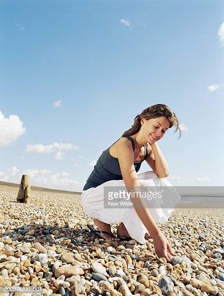 Young woman crouching on pebble beach, picking up pebbles, smiling