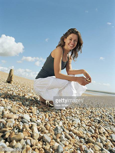 Young woman crouching on pebble beach, smiling, portrait
