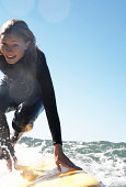 Young woman crouching on surfboard in sea, smiling