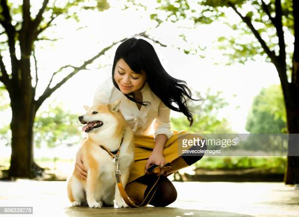 Young Woman Crouching to Pet a Dog
