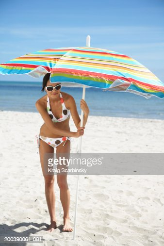 Young woman crouchng under beach umbrella, smiling, portrait
