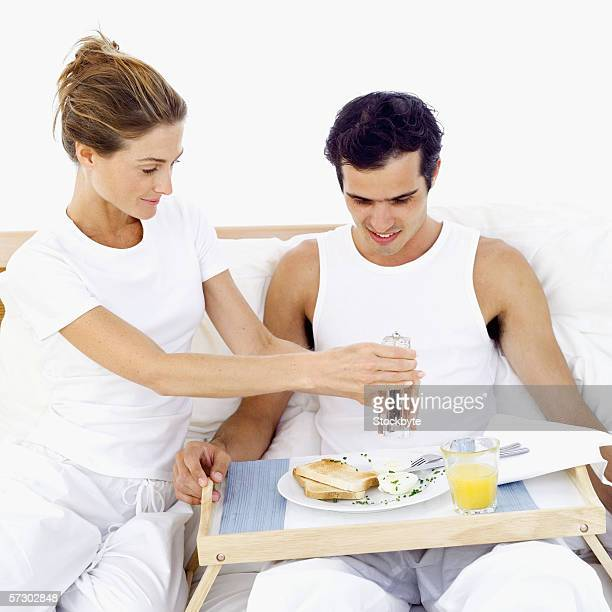 Young woman crushing pepper on a breakfast plate in a tray in a young man's lap