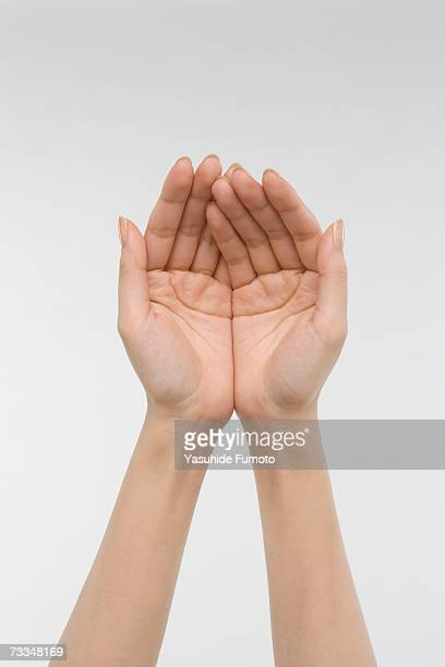 Young woman cupping both hands, close-up on hands