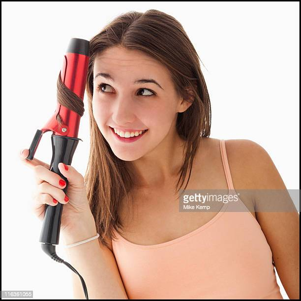 Young woman curling hair